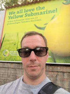 selfie of mpyne in front of an ad for a yellow submarine